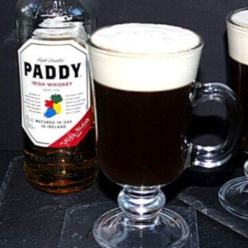 Glass of Irish coffee with a top layer of cream beside a bottle of whiskey