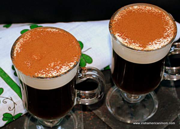 Two Irish coffees topped with cocoa powder