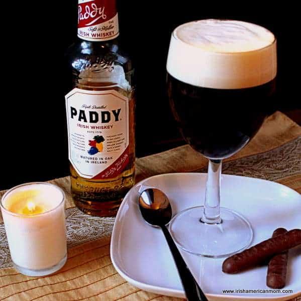 A glass of Irish coffee beside a bottle of Irish Paddy whiskey