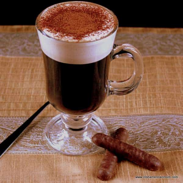 Irish coffee on a golden table cloth with two chocolate finger biscuits