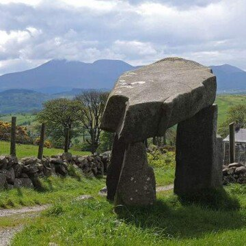 A large dolmen with three standing stones and a large capstone, with a mountain in the background