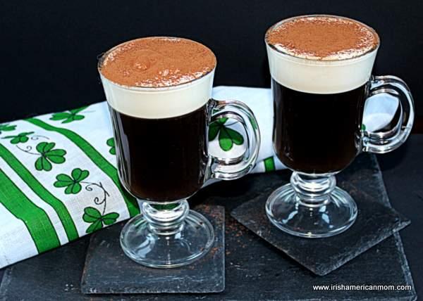 Two Irish coffees on a black slate with an Irish linen shamrock towel