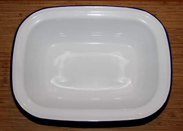 An enamel ware pudding basin is white with a navy blue rim.