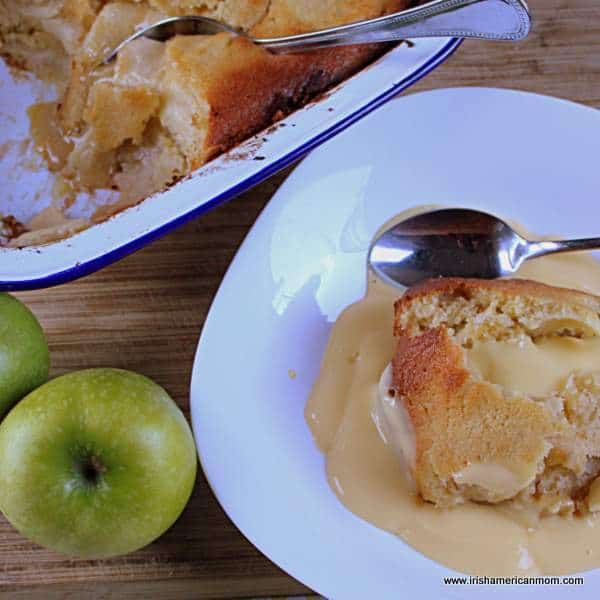 A serving taken from Eve's pudding and in a white bowl and topped with custard.