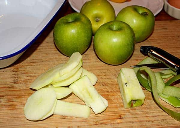 Green apples beside a sliced and cored apple with peels and a peeler on a chopping board.