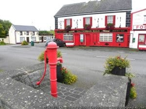 A red Irish pub opposite a red water pump