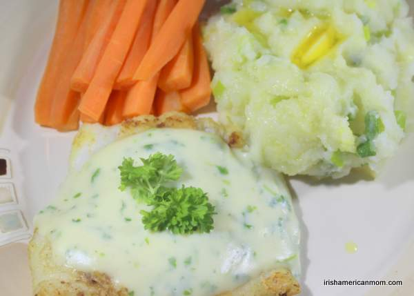 A serving of cod and parsley sauce with potato champ and steamed carrot sticks.