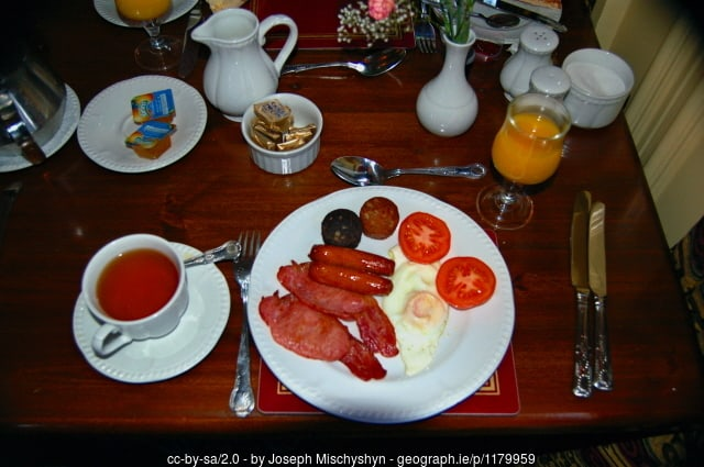 A table topped with a plate of breakfast foods, a cup of tea on a saucer and bowls and pitchers