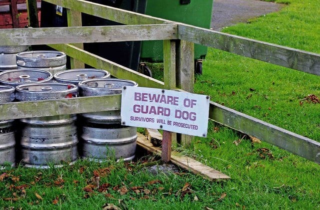 Beer barrels stored in a fenced area with a sign