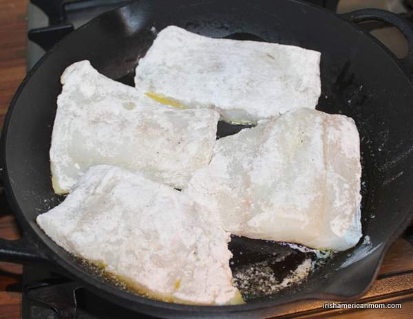 Four flour dredged cod pieces frying in a black cast iron skillet.