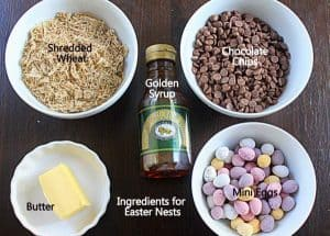 Ingredients needed to make chocolate Easter nests including bowls of shredded wheat, chocolate chips, butter, syrup and mini Easter eggs