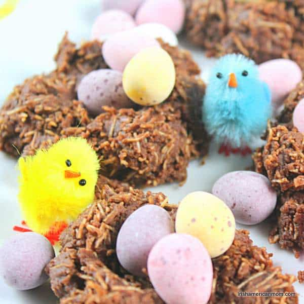 Decorative chickens beside chocolate nests with eggs