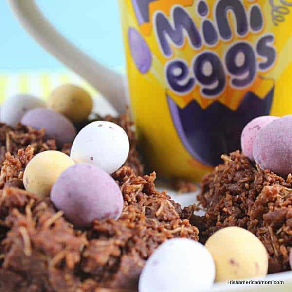 Mini eggs on chocolate nests beside a yellow mug