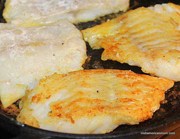 Golden fried cod fillets being turned for cooking in skillet.