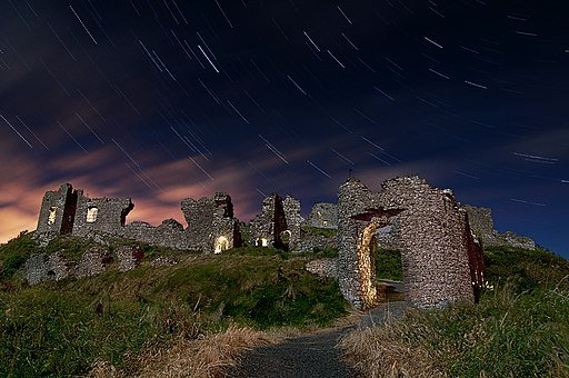 A ruined castle on a hill at night