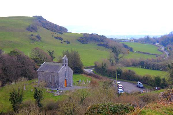 A church beside a green hill with cars parked beside it