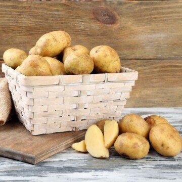Potatoes beside a cutting board with a basket of potatos