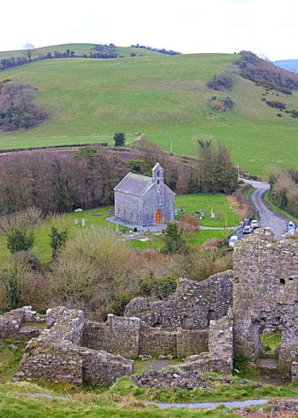 Looking down on a stone church from a ruined castle on a hill