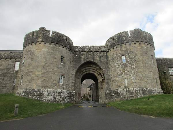 An old stone building with round towers and an arched entrance
