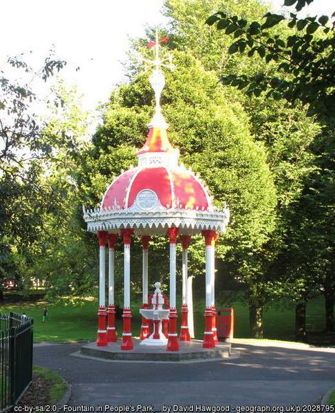 a red and white decorative fountain in a park with green trees
