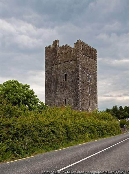 A large tall stone tower castle on the side of a road