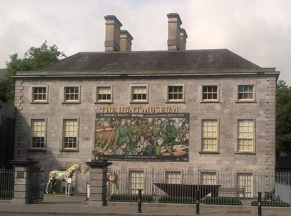 A large brick building with a mural and a horse statue