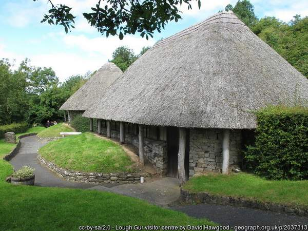 a stone hut style building with a straw roof
