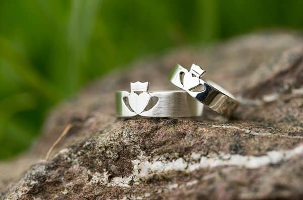 A close up of a rock with two silver Claddagh rings