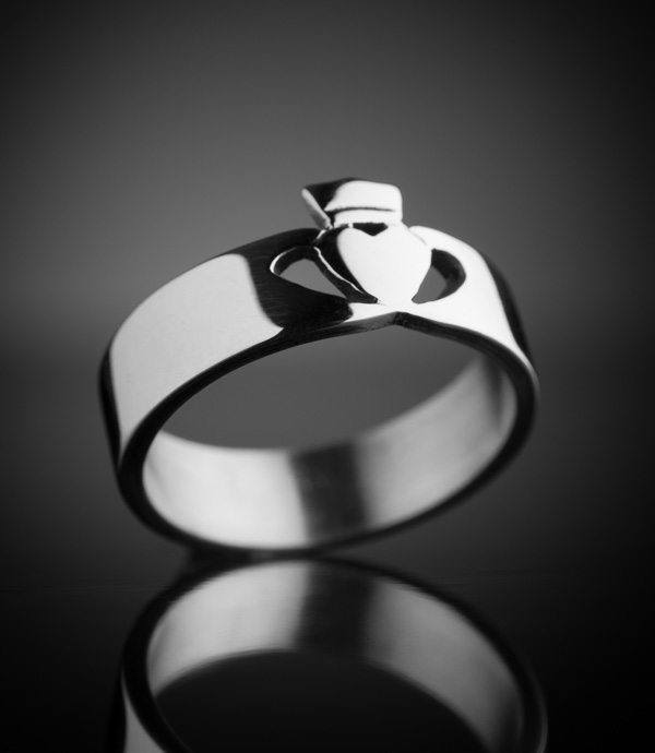 A close up of a silver Claddagh ring