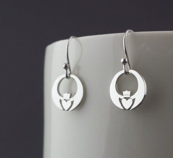 Claddagh design earrings hanging on a display