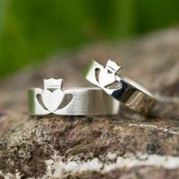 Two wedding bands featuring hearts with crowns displayed on a rock