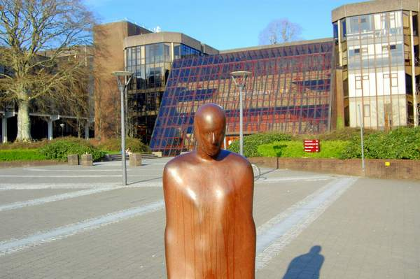 a sculpture of a person in front of a glass university building