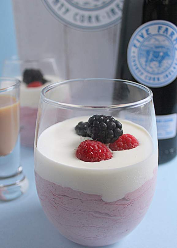 A close up of a glass of mousse with fruit on top