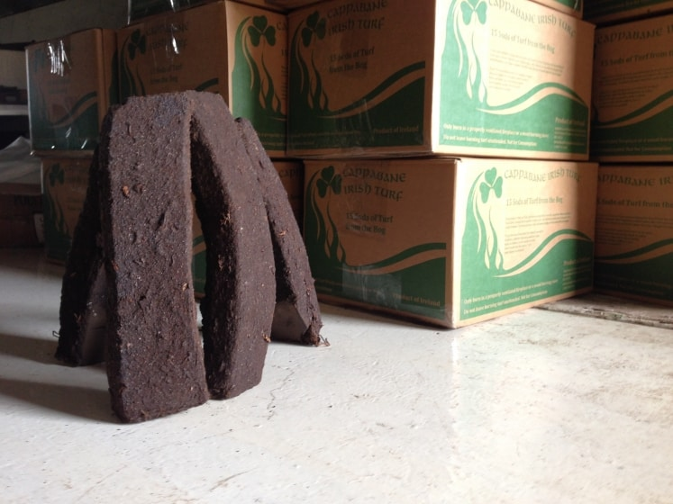 Peat or turf beside a stack of cardboard boxes