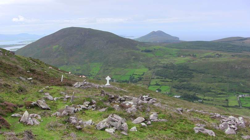 A mountain with a patchwork of green fields
