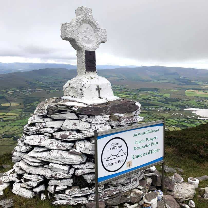A stone cross and sign on a rocky hill