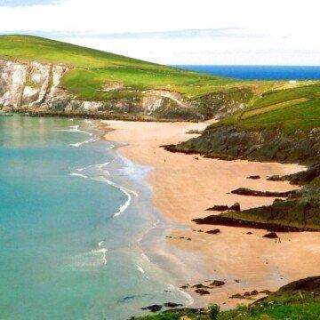 A sandy beach beside blue ocean waters