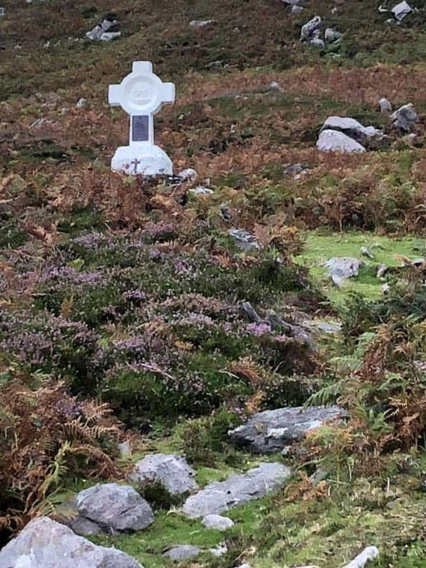 A white cross on a rocky hill