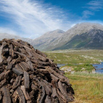 Stack of peat turf in a field beside mountains