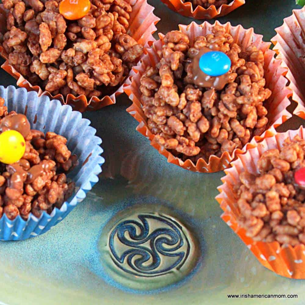 A plate of chocolate rice krispie cakes with colorful candies on top