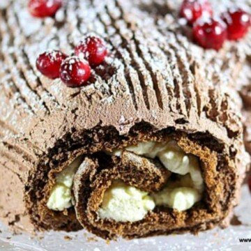 A chocolate roll up cake with whipped cream and chocolate frosting and cranberry decoarations
