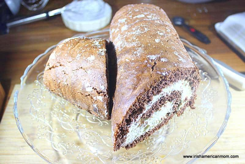A chocolate swiss roll with a piece cut off to form a log shape