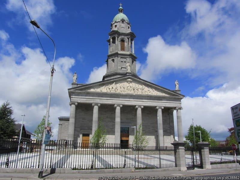 A clock tower on a church with tall pillars