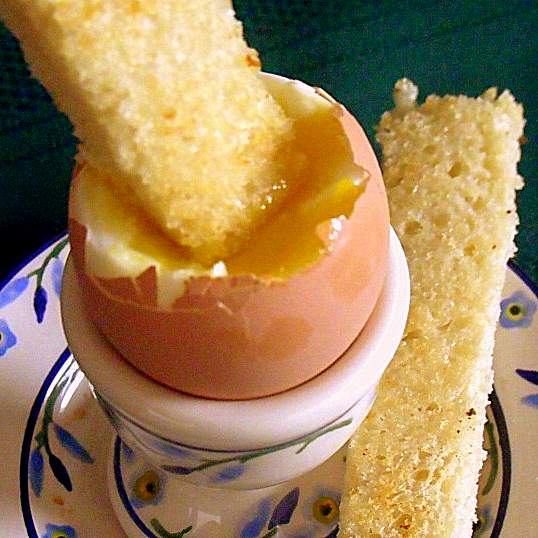 Dipping a bread soldier in soft boiled egg