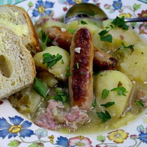 Dublin coddle sausage stew served in a bowl with crusty buttered bread