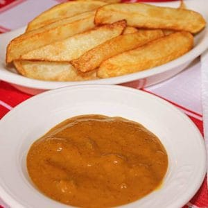 Chips and homemade curry sauce in white serving dishes