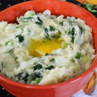 Irish Colcannon served in an orange bowl with melted butter
