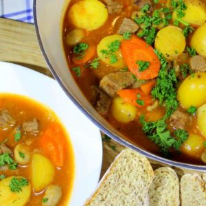 Irish farmhouse beef stew in a bowl with bread and a pot of stew