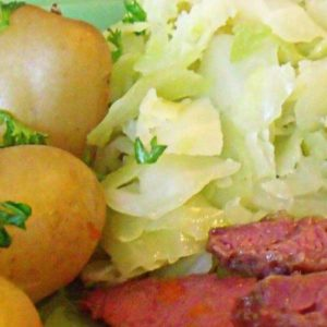 Boiled Irish cabbage on a plate with boiled potatoes and corned beef slices
