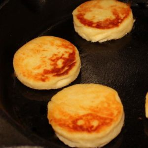Irish potato cakes in a black skillet being fried until golden brown